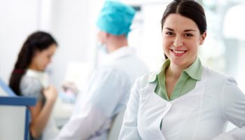 Pretty nurse looking at camera with smile on background of podiatrist and patient